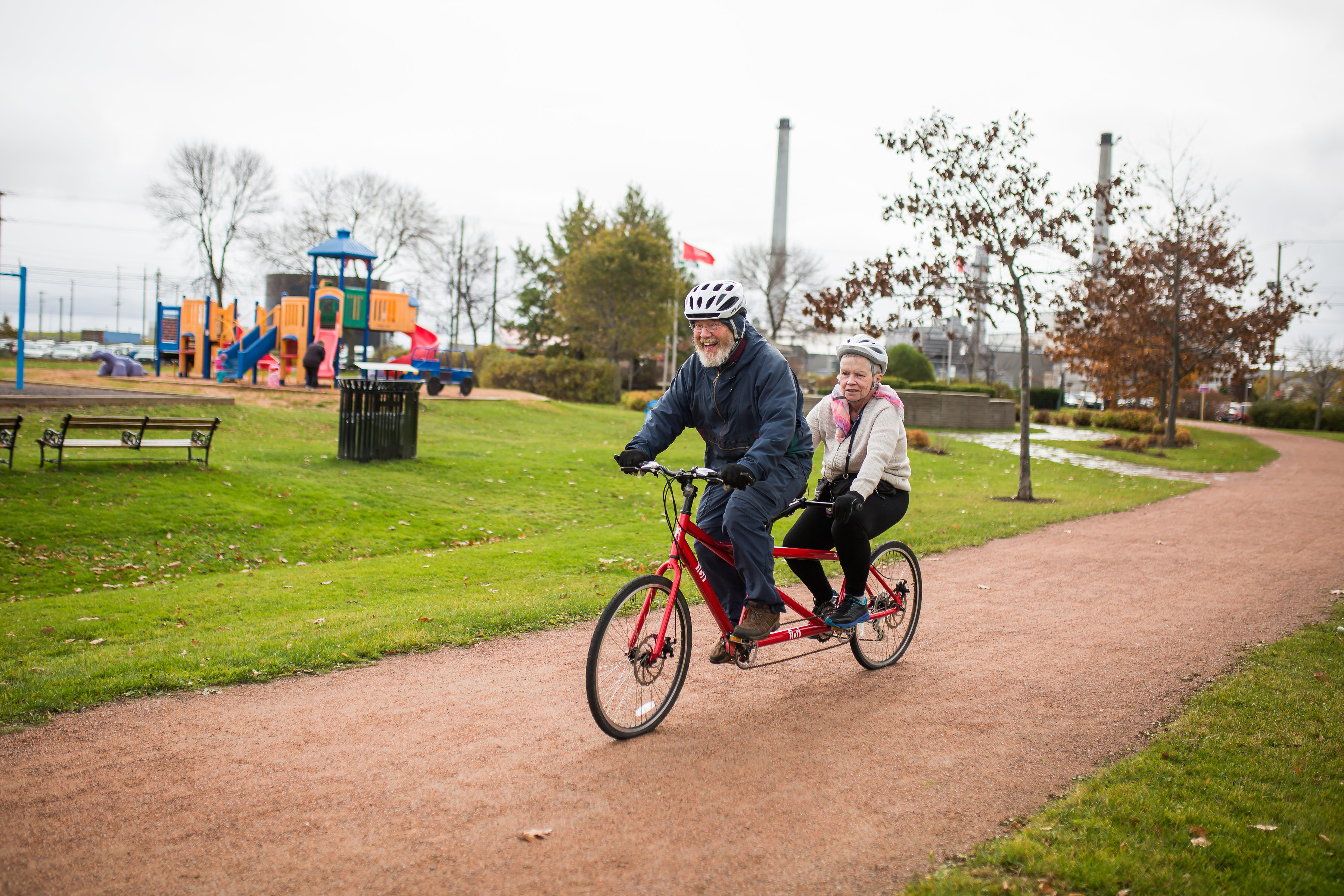 man and woman riding tandem bicycle through park, laughing