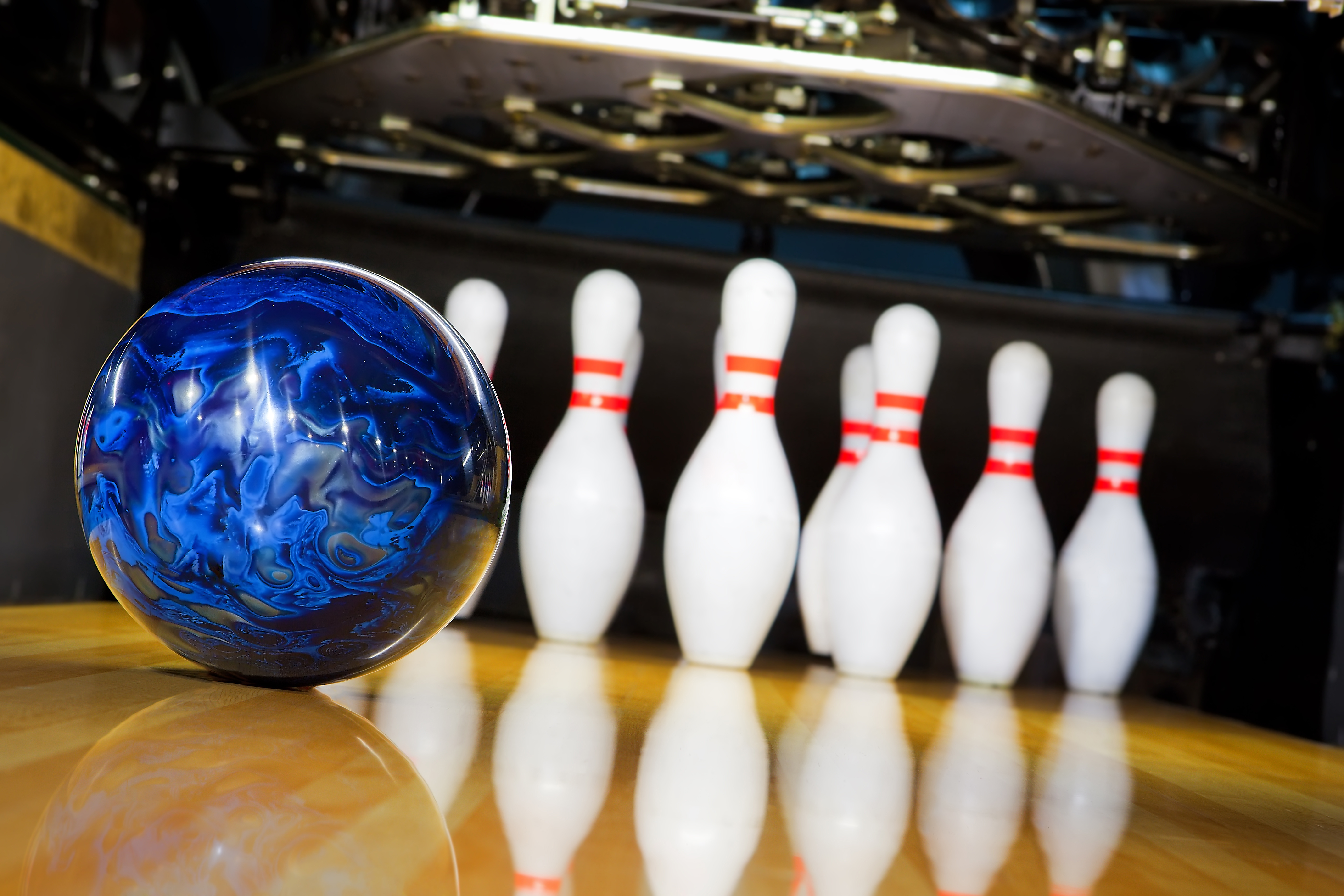 blue bowling ball rolling towards bowling pins