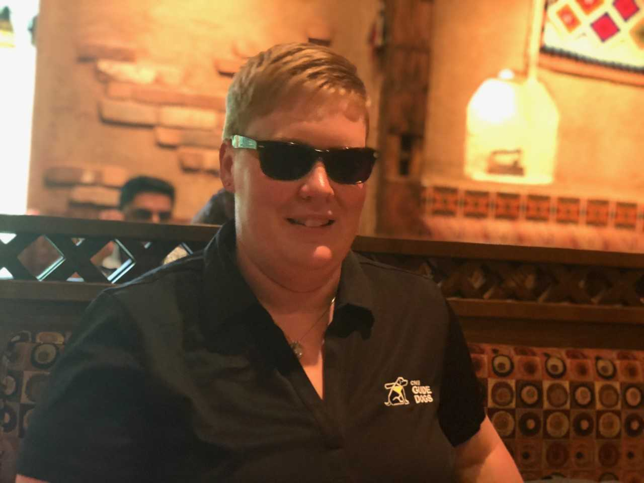 Ashley Nemeth smiles while sitting in a restaurant booth and wearing sunglasses.