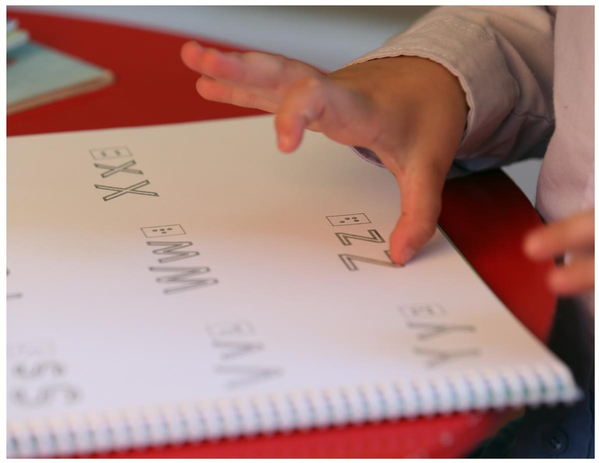 a close up shot of a hands reading braille.