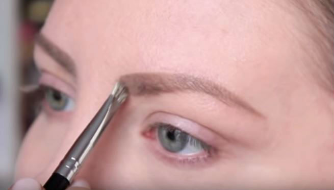 Woman colouring in her eyebrows