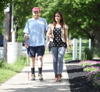 an older man holds a white cane and walks alongside a young woman. Both are smiling.