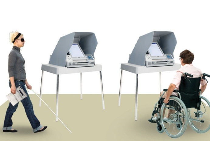 Picture of a woman with a cane walking past an Assistive Voting Device, next to a woman in a wheelchair using a second Assistive Voting Device