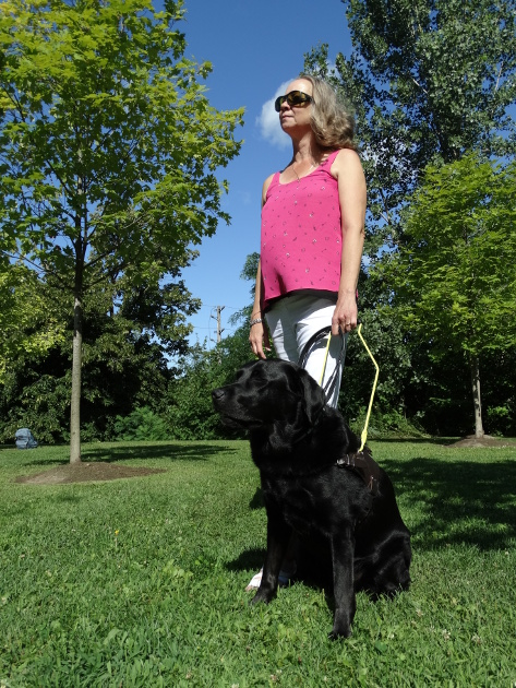 Cindy and her guide dog, Barney, photographed outdoors. Cindy stands in a triumphant pose - staring off into the distance. Barney, a black Labrador/Golden Retriever cross, sits at her feet. She is holding his harness.