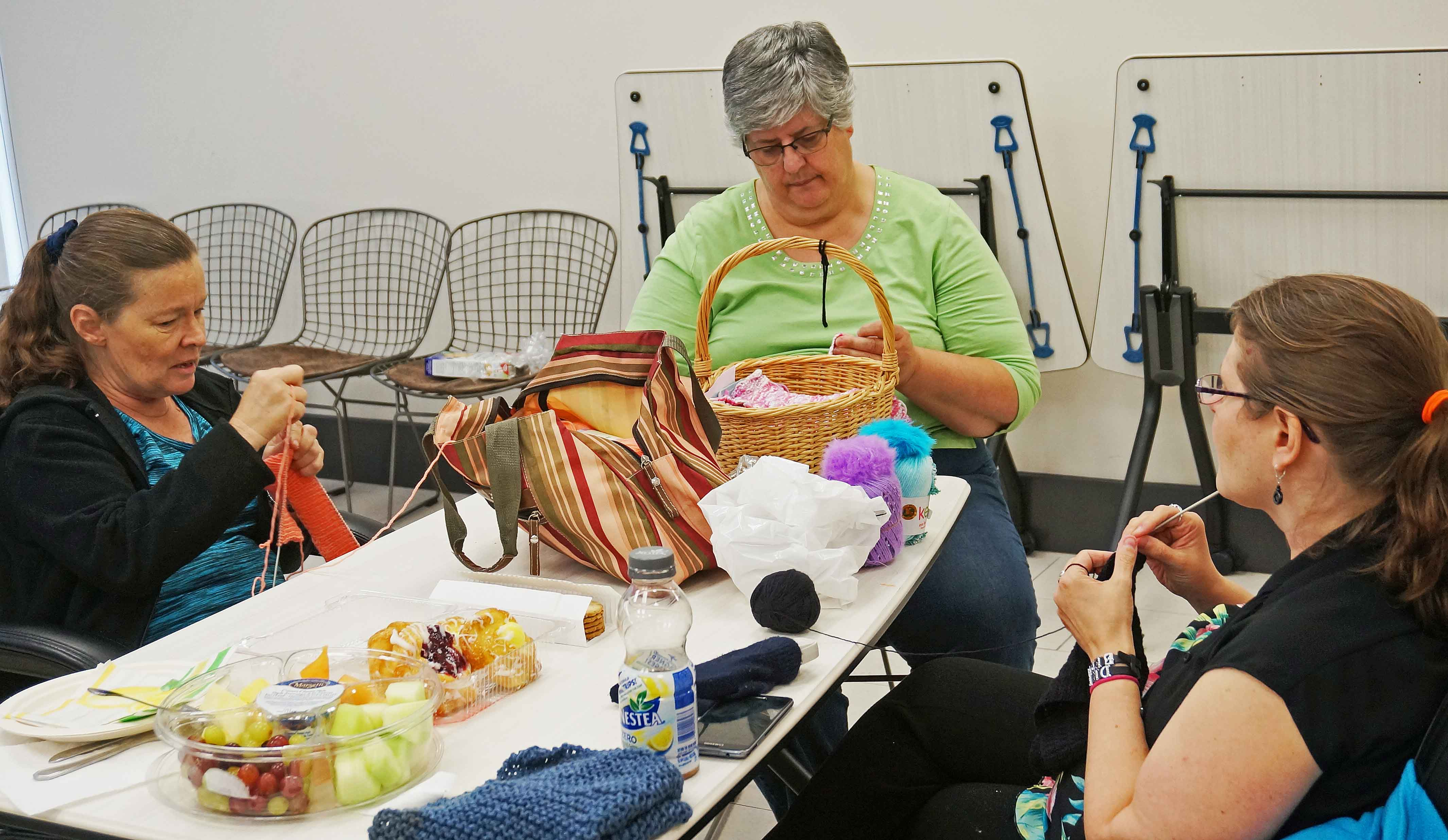 three women sitting at tables together, knitting and talking