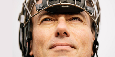 A close up of a man's face, with a hockey helmet on his head.