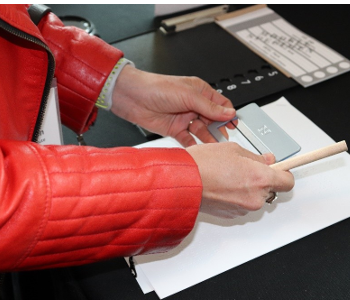 A woman holds a signature guide and a large grip pencil over a piece of paper. Beside her is a large print ballot and tactile voting template.