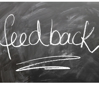 "A dirty chalkboard with white text written in chalk on it. Text ""Feedback."""
