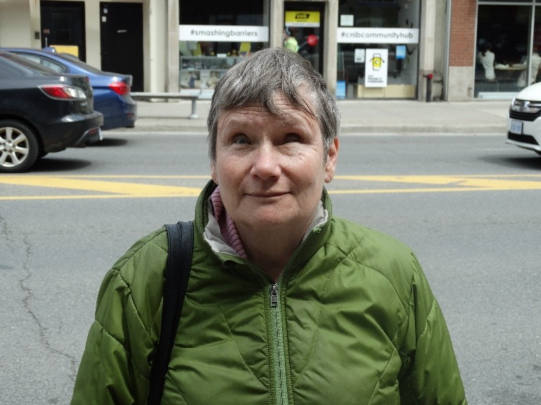 A photo of Debbie Gillespie standing outside the CNIB Toronto Community Hub.