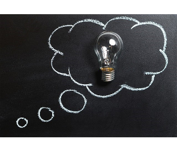 Chalkboard art. A lightbulb sits on top of a chalkboard. Surrounding the lightbulb is a chalk illustration of a thought cloud bubble.