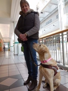 Sharon Ruttan standing with her guide dog, Hominy, sitting and looking up at her.