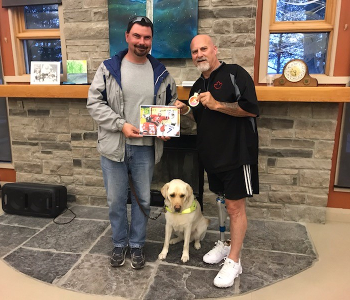 Guy Carriere & his guide dog (left) and Paul Rosen (right) pose for a photo together. Guy is holding an autographed picture of Paul and Paul is displaying a medal in his left hand.
