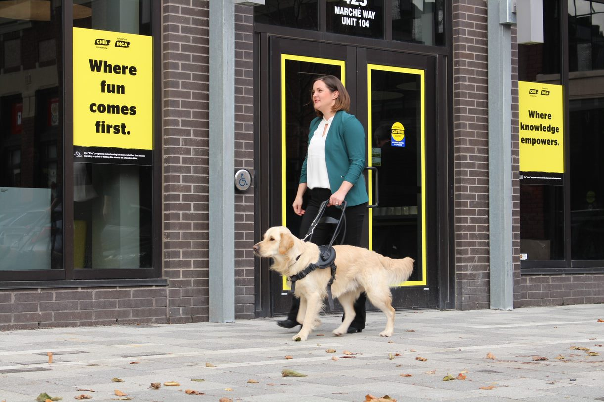 Photo of Erin & Winston walking along a sidewalk in front of a CNIB Foundation building.