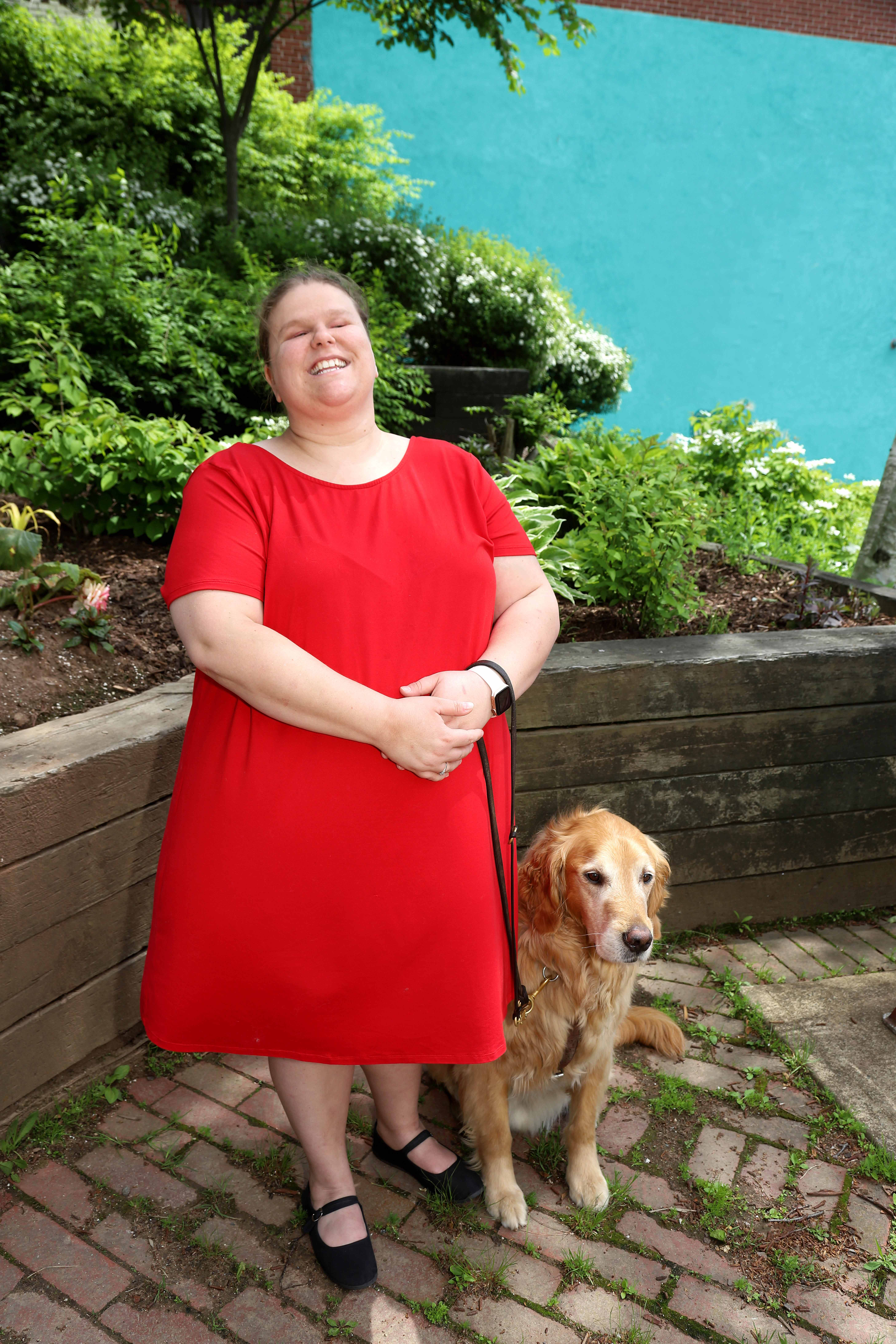 Jennifer MacNeil, standing outside on a sunny day, smiling for the camera with Lenny, her guide dog.