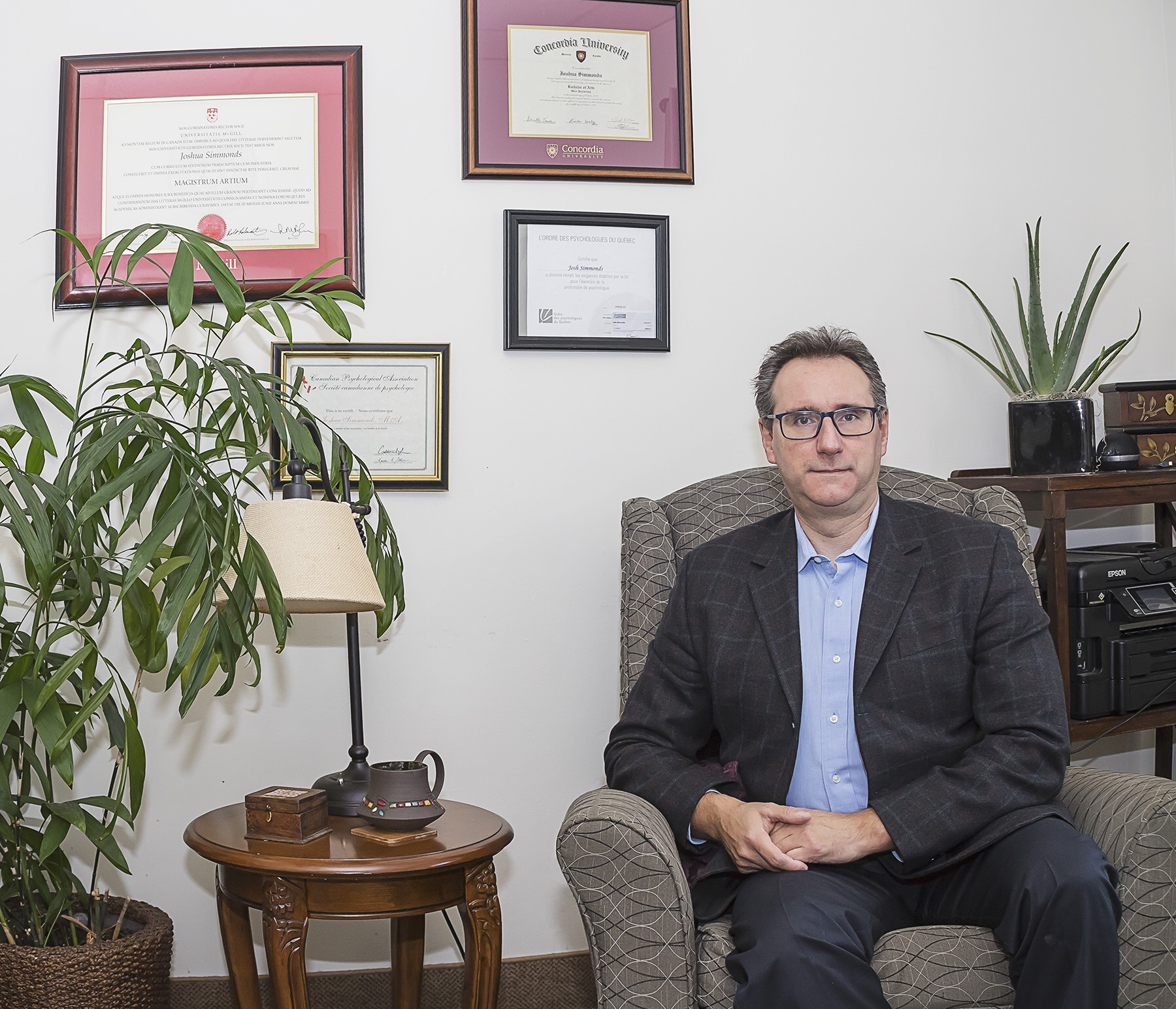 Joshua Simmonds, wearing a suit, sits in a chair in his office. There are certificates on the wall and plants and a coffee table beside him.