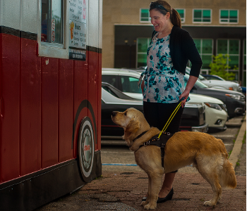 Larissa stands with Piper (a golden guide dog)in front of a chip truck. Piper is in harness.