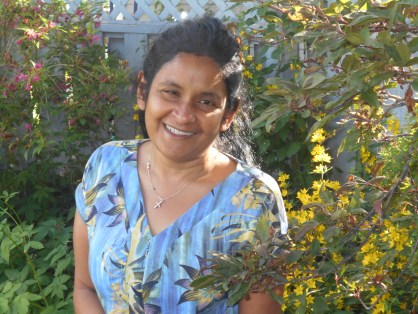 Tara Nanayakkara smiles and stands among flowers in a garden.