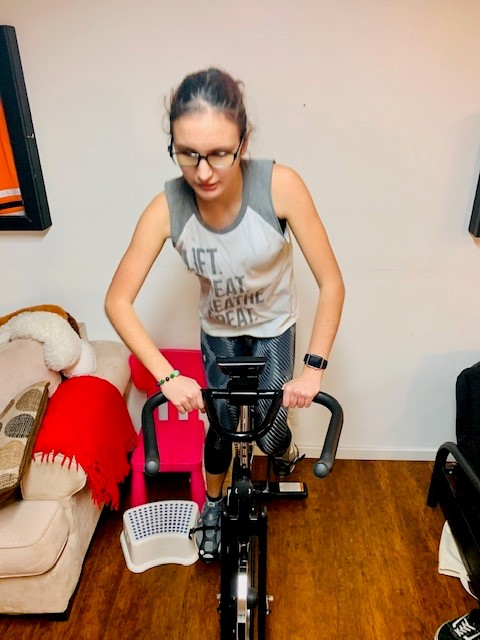 Veda, wearing athletic clothes and glasses, rides her indoor spin bicycle.