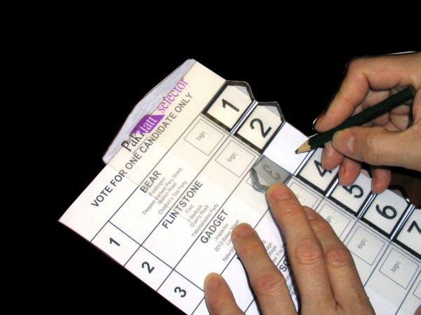 A hand using a pencil is marking a ballot using a braille template