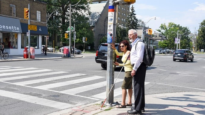 Photo of man with white cane standing at an intersection.