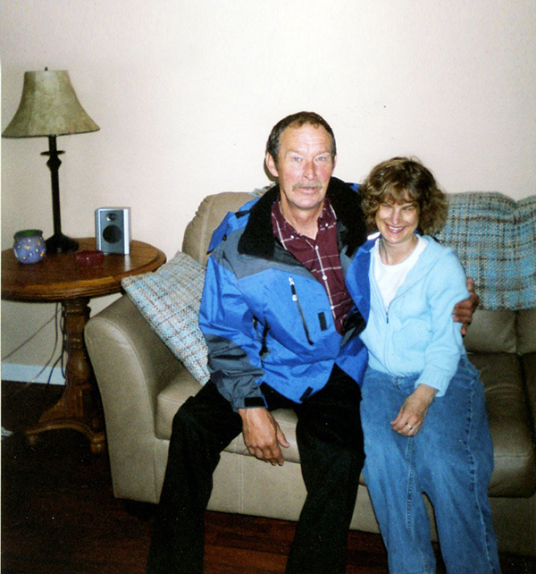 Holly Bartlett smiling, arm-in-arm with her father in a living room