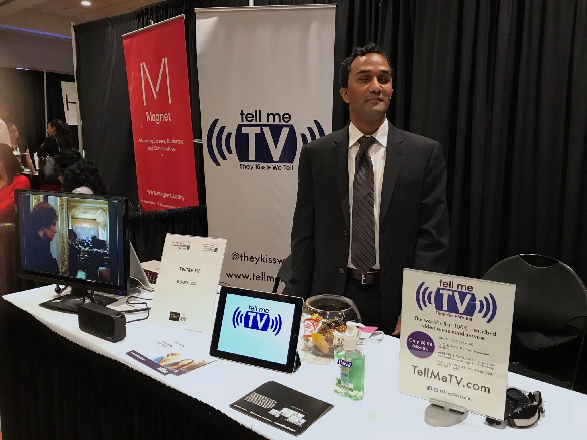 Kevin Shaw stands at a table where he has a display set up for his company, TellMeTV.