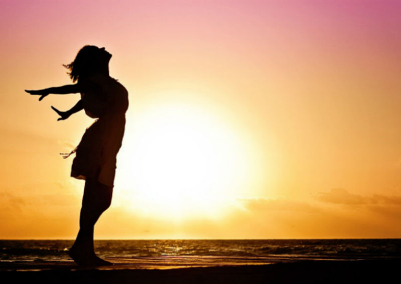 A woman stands silhouetted against a sunset, arms outstretched