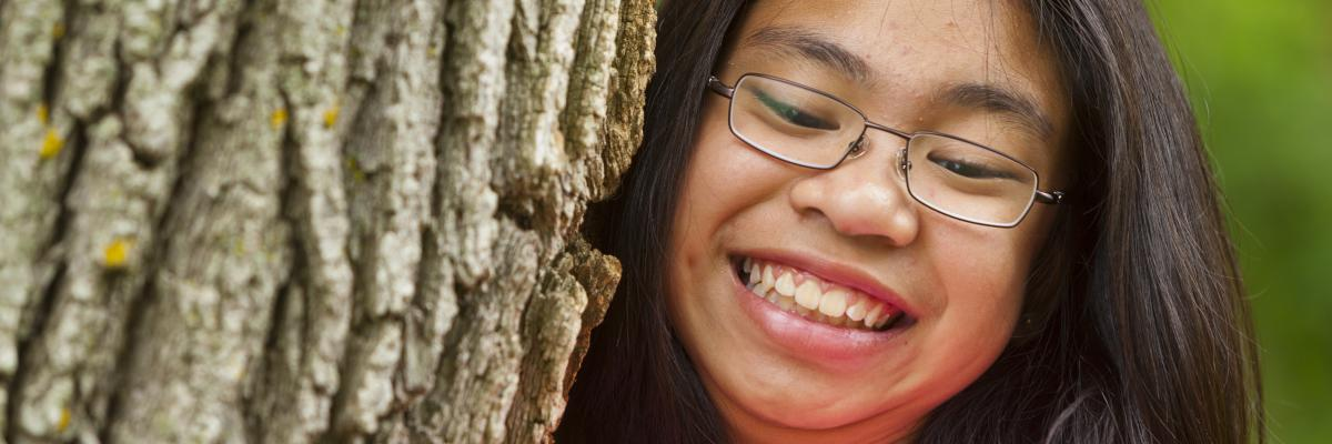 A close-up of a girl climbing up a tree, smiling at the camera