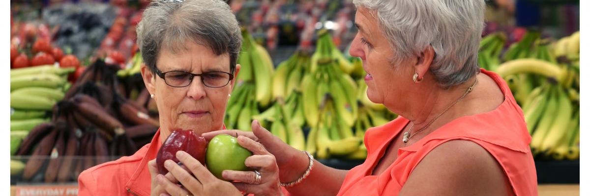 Two woman, wearing coral-coloured tops, are shopping for apples.
