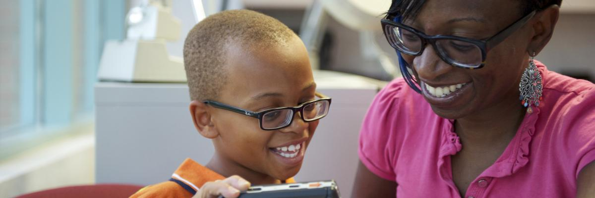 A young boy and his mother, both wearing glasses, interact as the little boy plays with a magnifier.
