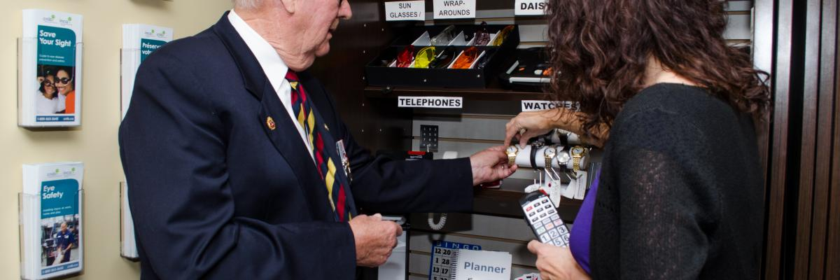 A volunteer shows a participant Shop CNIB products on display.