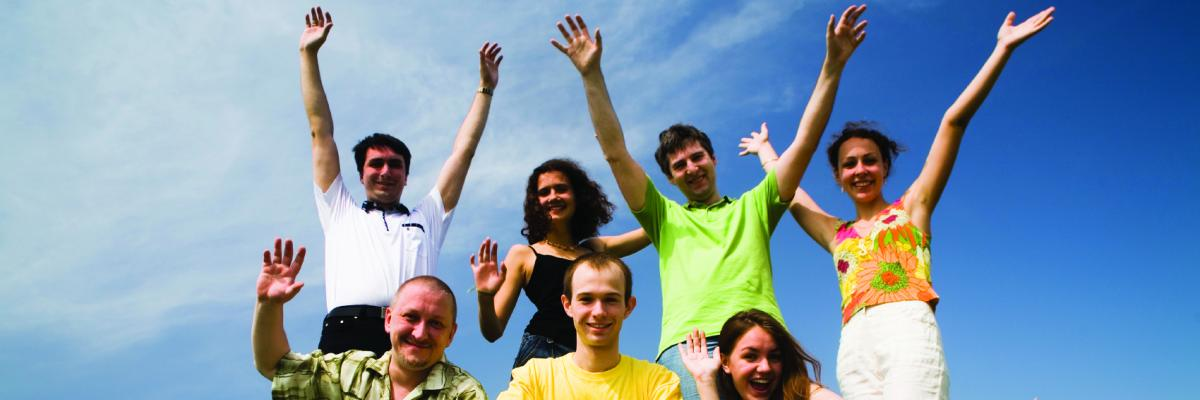 A group of people standing on a hill with their hands in the air