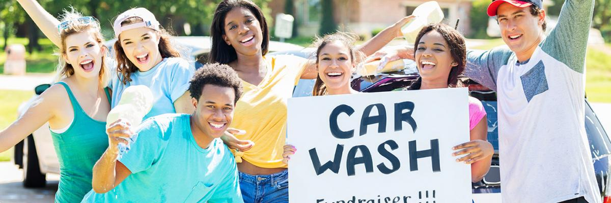 Group of individuals cheering with car wash sign