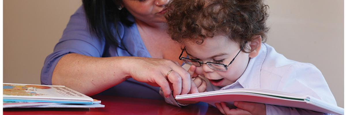 a mother and child read a tactile, braille book.