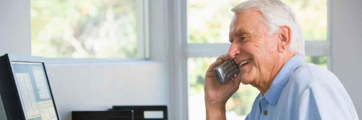 Elderly man talking on his phone in home office