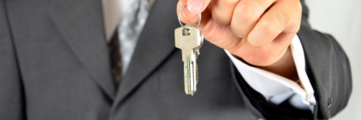 man in suit holding a set of keys