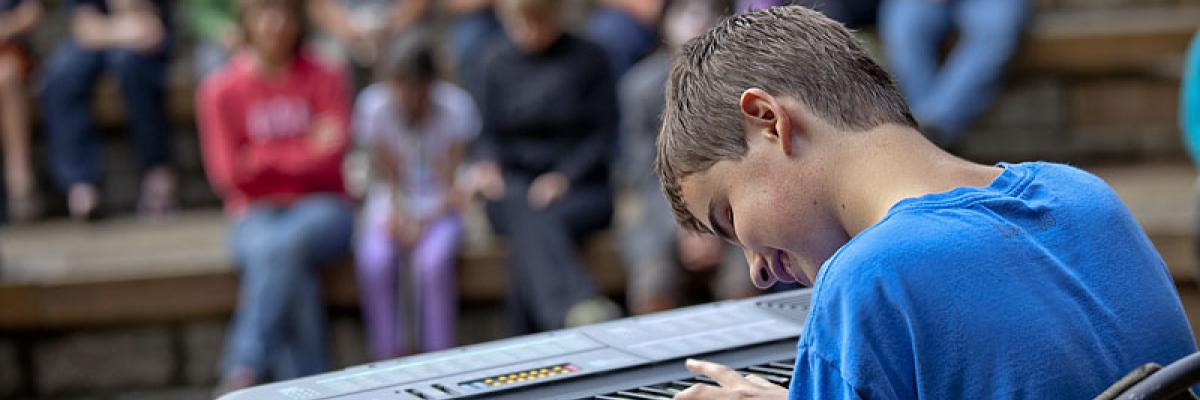 boy with sight loss playing keyboard for a crowd