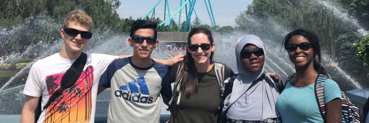 A group of smiling teenagers and a volunteer at Canada's Wonderland.