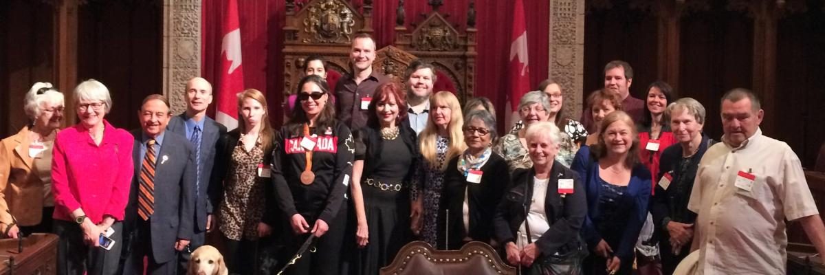 CNIB staff and clients stand with Senators in front of the Senate Thrones and Speaker's Chair.