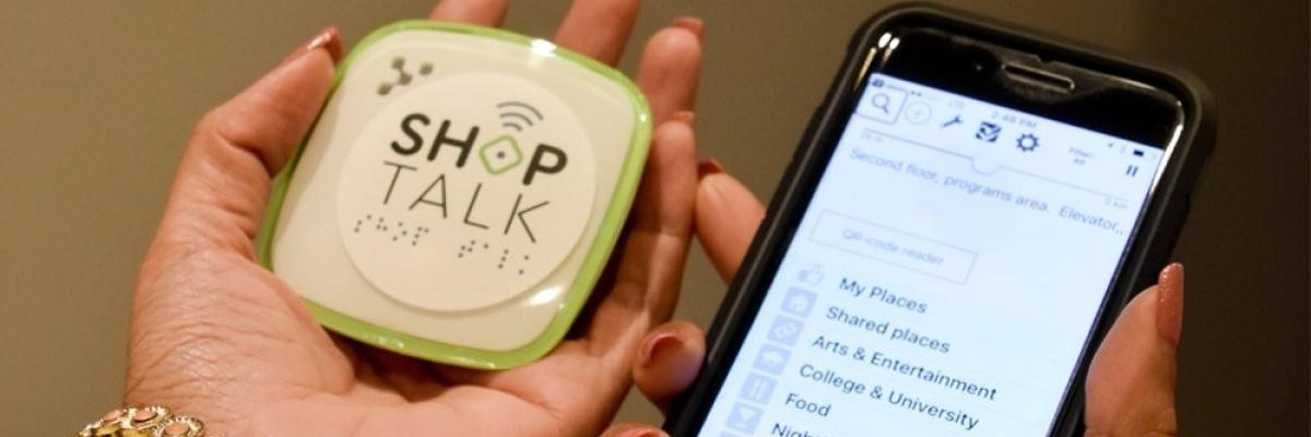 A woman holds a smartphone and Shop Talk Blind Square technology, which allows people to navigate using their mobile devices.