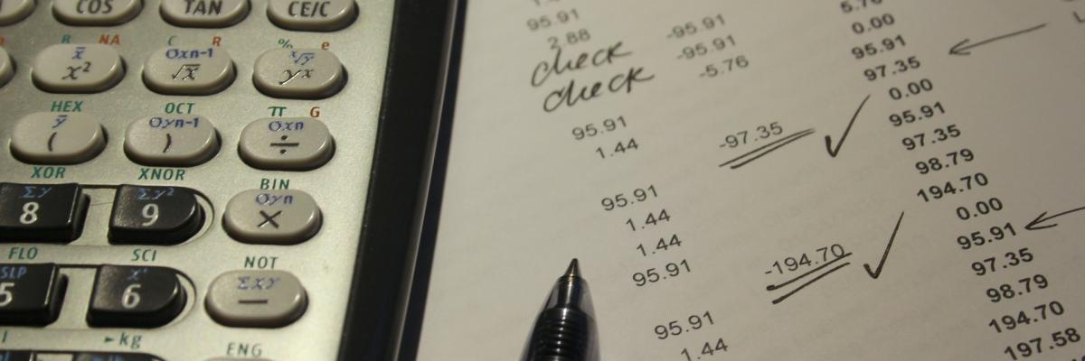 Image shows a pen and calculator on a budget statement.