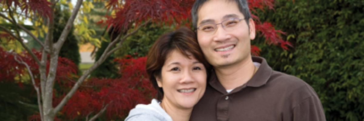 middle-aged couple standing outside smiling