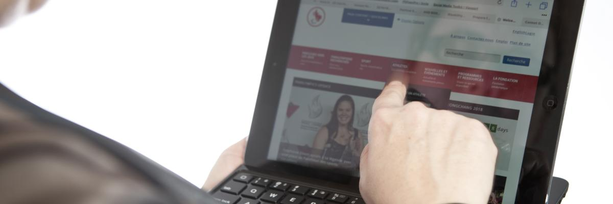 an over-the-shoulder shot of a client tapping an iPad.