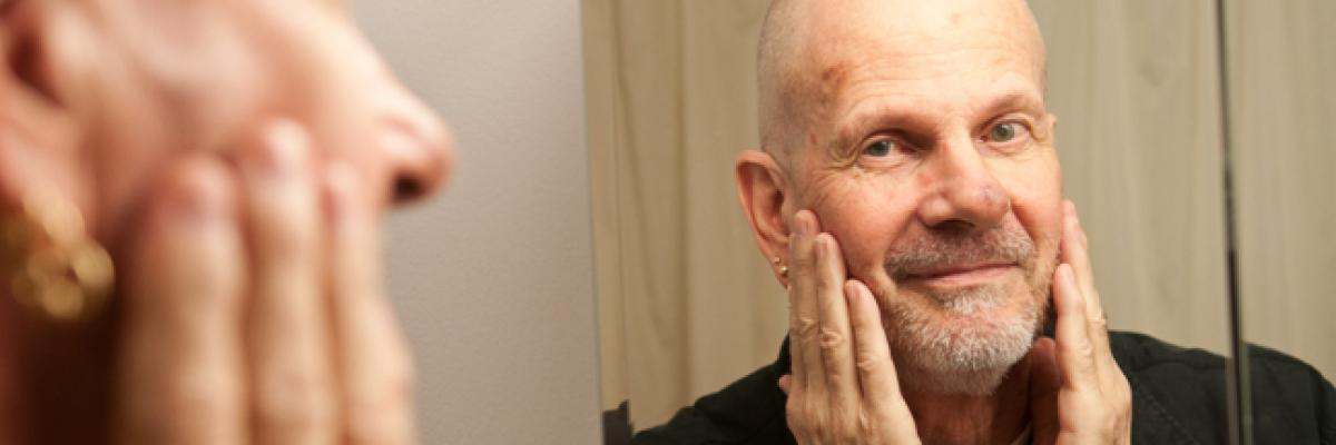 Bald gentleman with goatee looking in mirror.