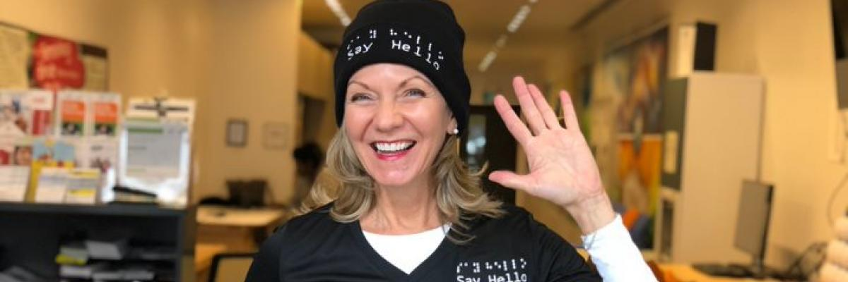 Say Hello 2 Blindness founder Denise Justin smiles and waves while wearing her company-branded shirt and toque.