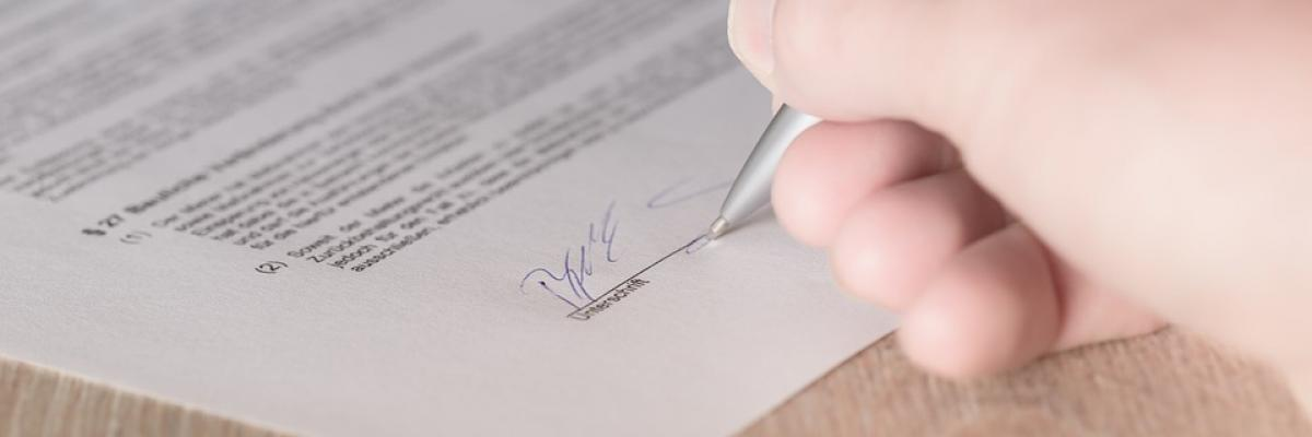 A woman's hand is shown signing a contract.