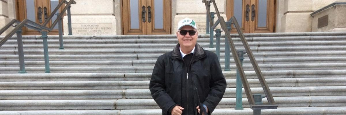 Bob Huber stands outside of the Saskatchewan legislative building with his two dogs, smiling with his sunglasses on and green Roughrider ball cap.