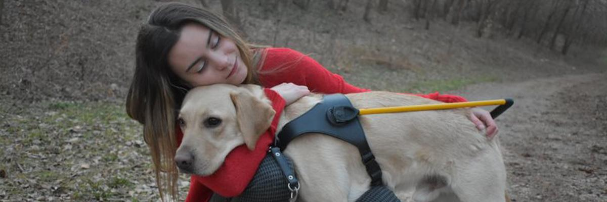 Danika hugging a Lab/Golden Retriever cross in a yellow harness.