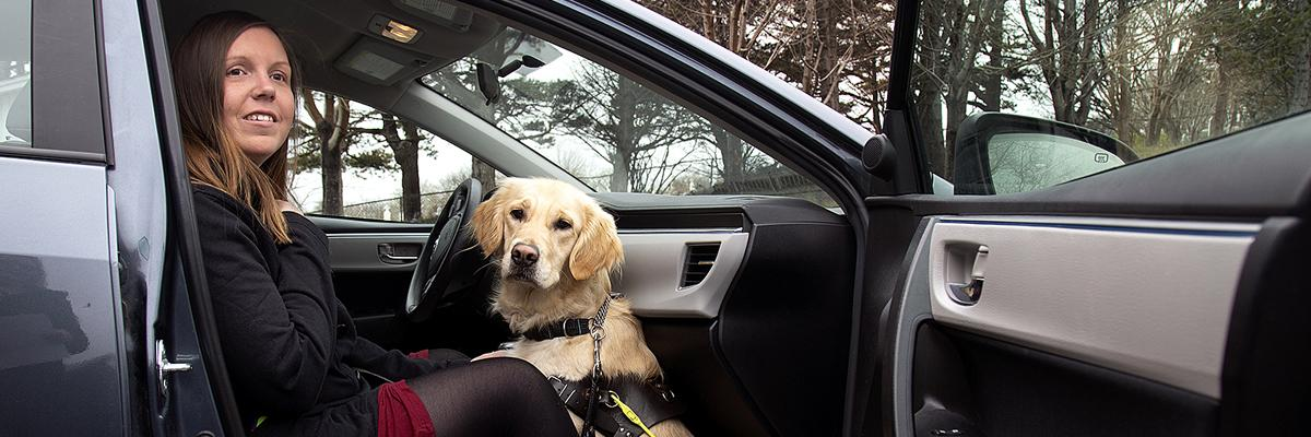 A woman and her Golden Retriever guide dog sitting in the passenger seat of a car.