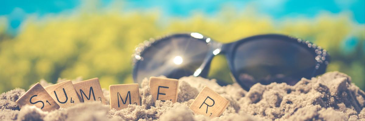 "Scrabble tiles spelling out ""summer"" on the sand; sunglasses behind them."